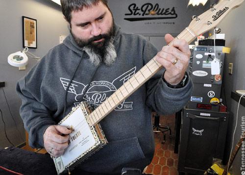 Gitarrenbauer Greg Mitchell demonstriert eine von ihm gebaute Cigar Box Guitar